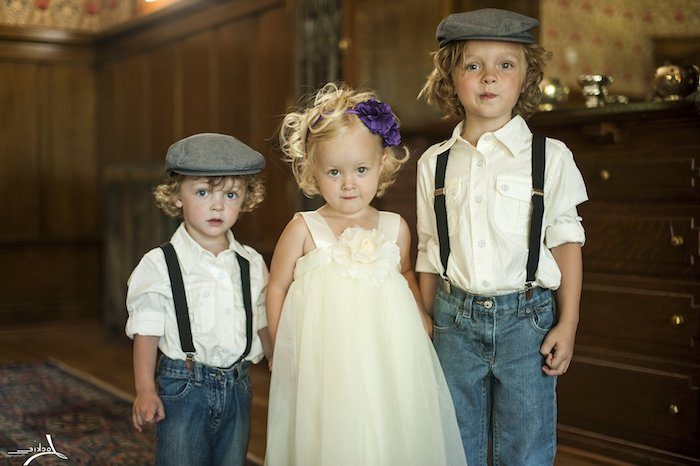 kids dressed in semi formal clothing, garden party attire, two boys wearing jeans, with white shirts and suspenders, and grey vintage berets, and a little girl in a cream dress, with a purple flower ornament in her hair