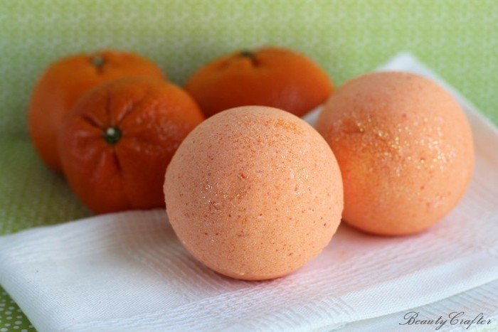 napkin in white, with two pale orange bath bombs, three clementine oranges in the background