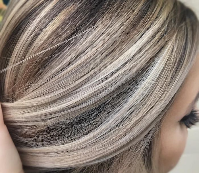 ash blonde streaks, on dark brunette hair, worn by young woman, with faux eyelashes, seen in close up, light brown hair with blonde highlights