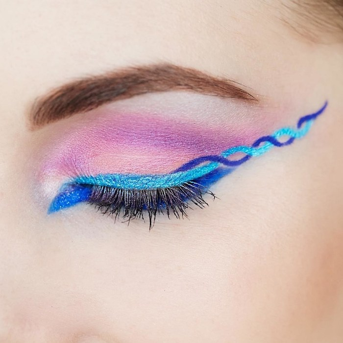 festival makeup, closed eye with pink eye shadow, pale blue and violet eyeliner, or eye pencil, in a swirly pattern