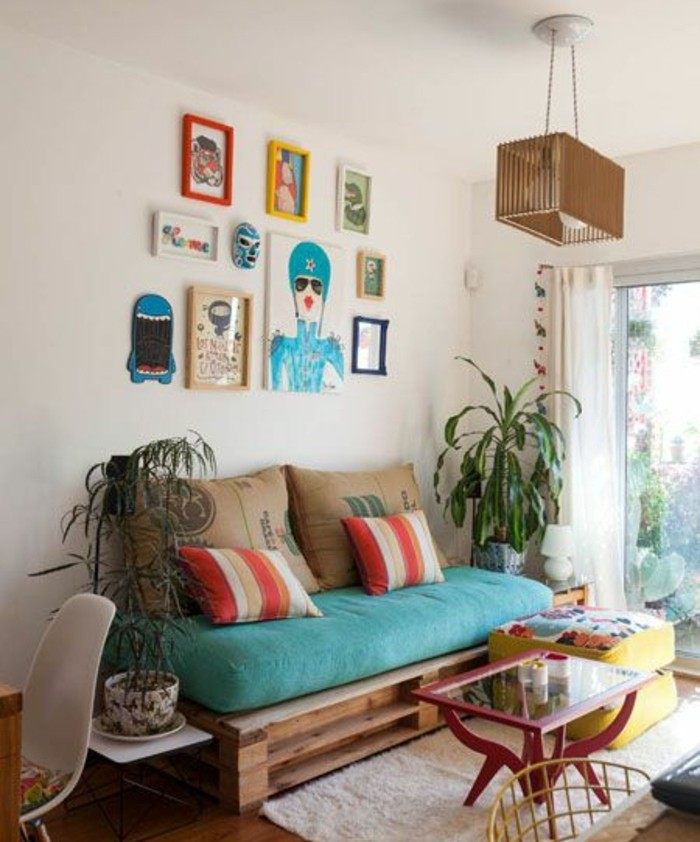 potted plants and colorful framed artworks, near a diy pallet couch, decorated with a large turquoise pillow, and several cushions
