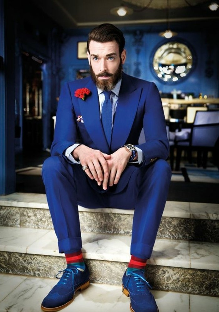 accents in red, worn by a bearded man, in a vivid blue suit, with white shirt, blue shoes and a blue tie, red boutonniere and socks
