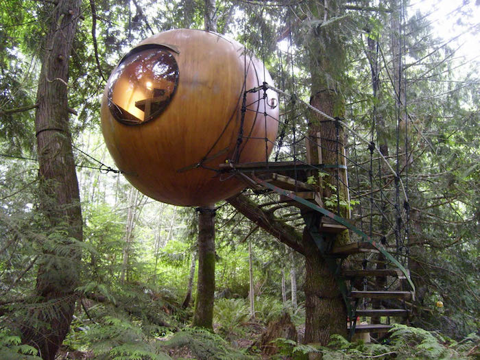 sphere made of wood, with a circular window, suspended from several fir trees, and accessible through a set of stairs