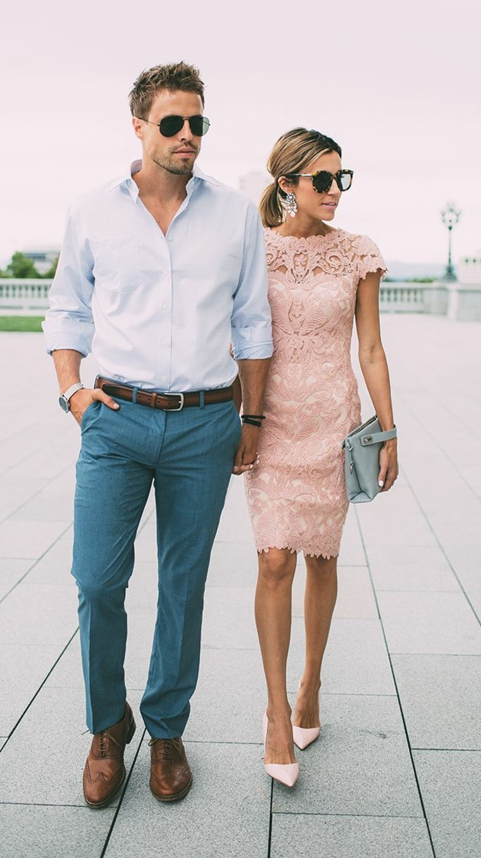 woman in pale pink, midi lace dress, walking hand in hand, with a young man, in pale blue shirt, and blue trousers, mens casual summer wedding attire, brown brogue shoes