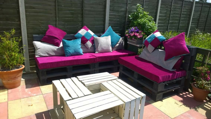 garden with furniture made from pallets, black painted wooden pallets, covered with fuchsia sofa cushions, and smaller cushions, in different colors and patterns