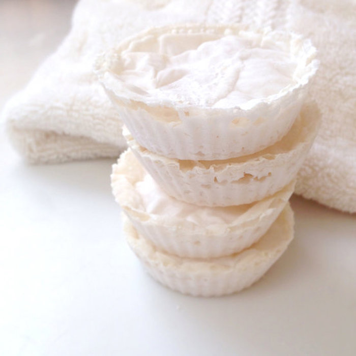 stacked foamy bath bombs, in creamy white, made to look like little tartlets, placed on white surface, near a white fluffy towel
