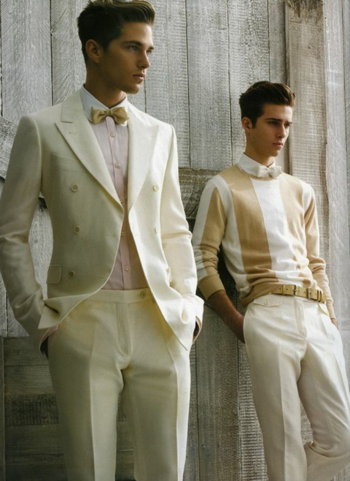 ivory two-piece suit, worn with a white shirt, and a mustard yellow bowtie, by young brunette man, black tie optional wedding, man next to him is wearing a white, and mustard yellow striped jumper, with white trousers