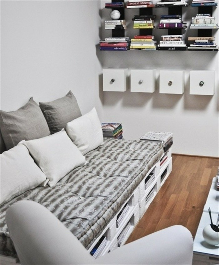 grey and white couch, made from white painted pallets, and textiles in soft grey tones, how to make pallet furniture, several bookshelves nearby
