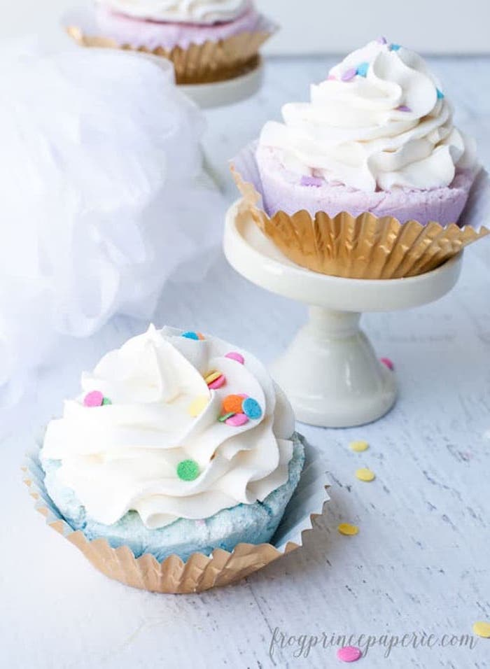frosted cupcake-style homemade bath bombs, in blue and pink, with white topping, and decorated with multicolored confetti
