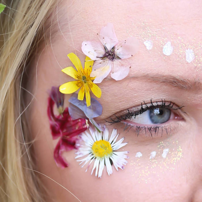 several different pressed flowers, stuck near the eye of a blonde woman, wearing black mascara, makeup looks, several spots of white paint