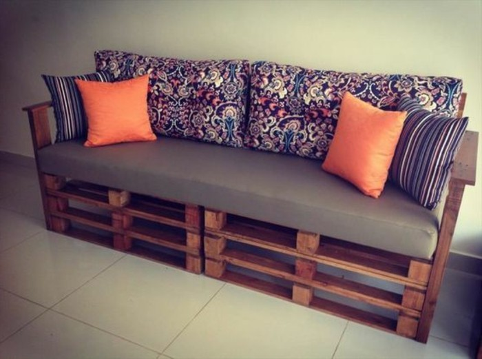 folk-inspired dark floral pattern, on the backrest cushions, of a diy sofa, made from dark brown wooden pallets, decorated with two sets of cushions