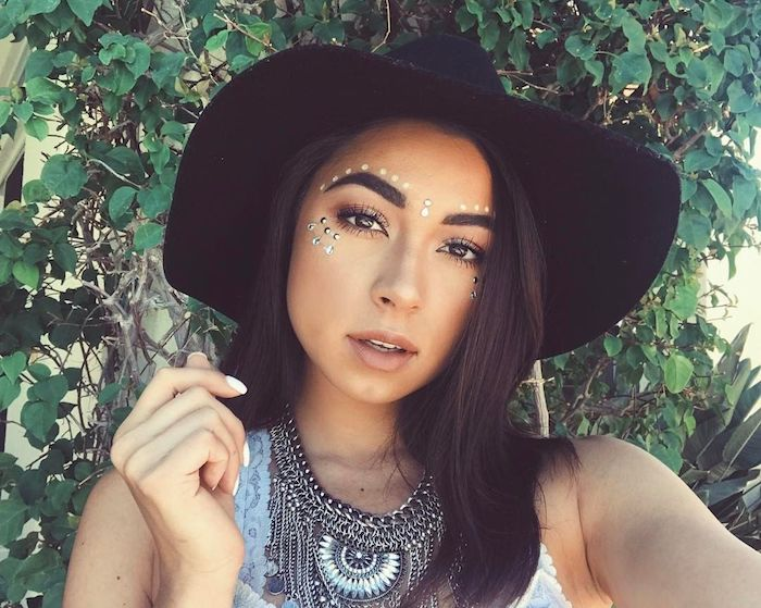 hat in black, worn by brunette woman with dark eyes, discrete and natural make up, decorated with white face paint, and silver pearl stickers, cute makeup looks, boho clothing and jewelry