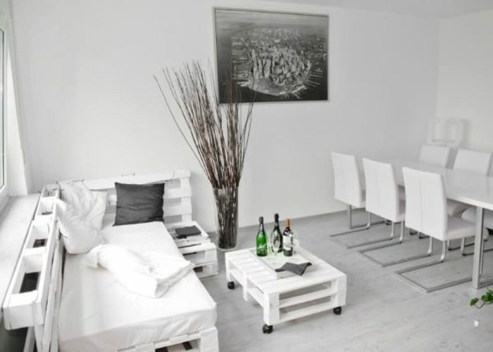minimalistic interior in white and pale grey, modern dining table with six chairs, pallet sofa and a matching coffee table, large grayscale photo on the wall, decorative dried branches in a vase