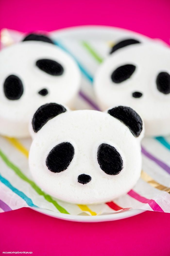 panda bear diy bath bombs, in white and black, placed on multicolored striped paper, placed over a white dish