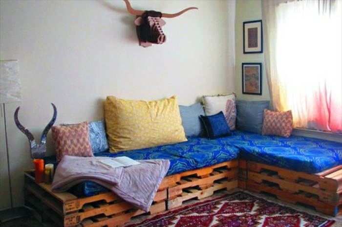 ornamental rug in red and white, near a corner pallet couch, decorated with blue patterned fabric, and several different cushions