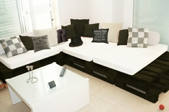 black and white corner sofa, with many cushions in grey, white and black, in different sizes, and featuring different patterns, furniture made from pallets, modern white table nearby