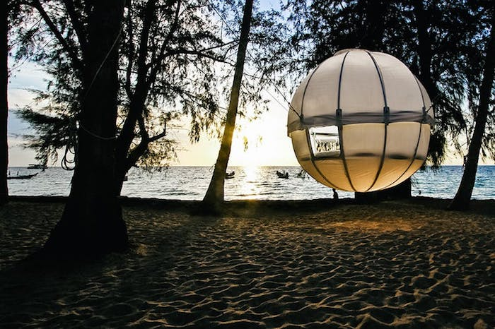 beach treehouse, round white orb, hanging above the ground, suspended from several trees, growing on a sandy shore, near the sea