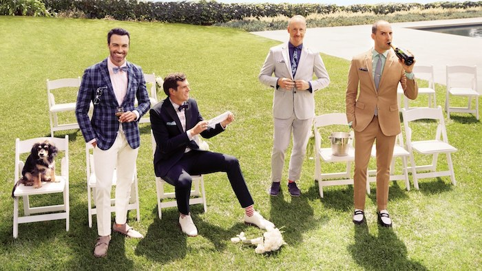 four men in semi formal clothes, and a dog, standing on a green lawn, near several white chairs, one of the men is sitting, dressy casual men, checkered blazer and white trousers, suits of different colors, garden chic wedding dress code
