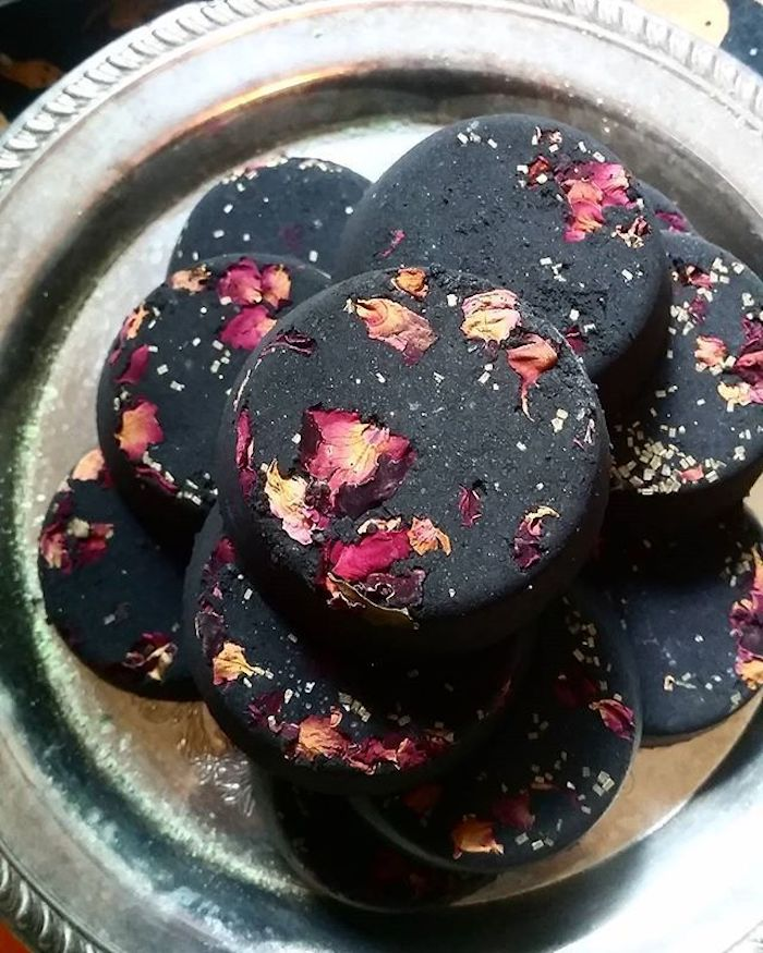 flat bath bombs in black, with dried rose petals, in yellow and different shades of pink, placed on an ornamental, round silver tray