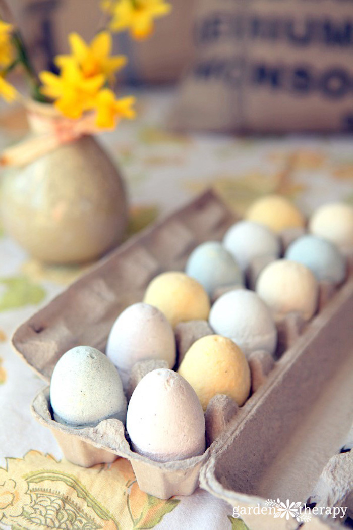 festive easter-themed bath bombs, shaped like eggs, in pale pastel colors, twelve in total, placed in a cardboard box