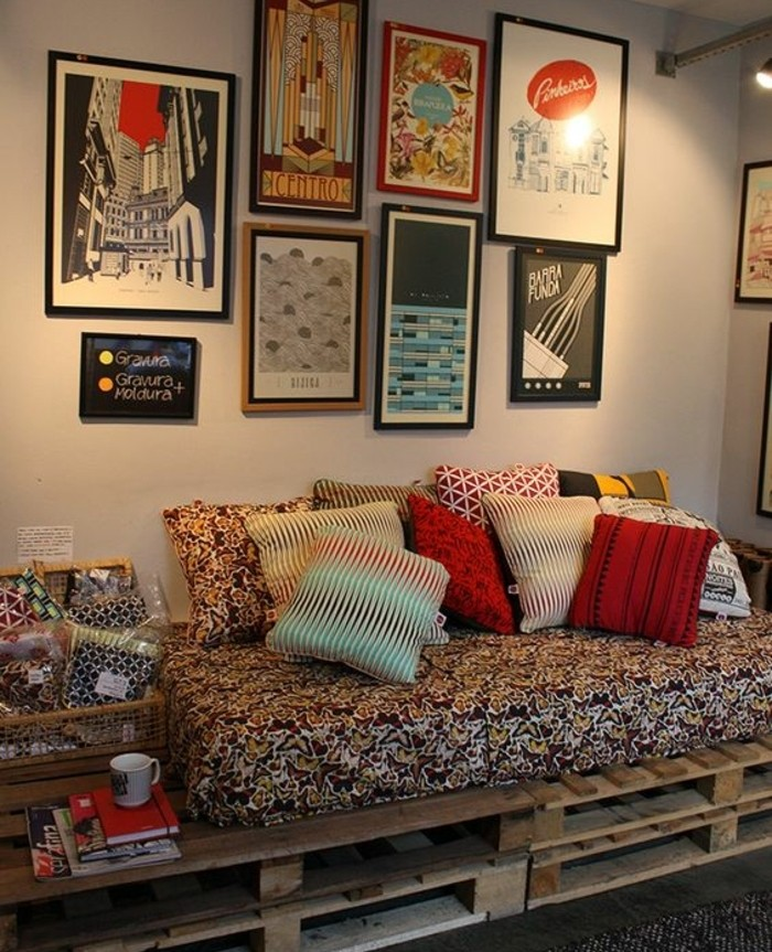 posters covering a wall, near a pallet sofa, mattress with multicolored cover, and several cushions, with different colors and patterns