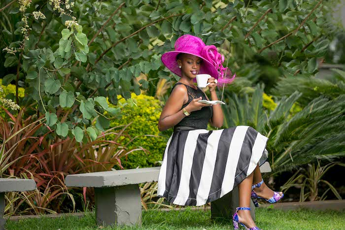 hot pink fancy hat, worn by woman, sitting on a stone bench in a garden, wearing black and white striped dress, and multicolored high heel sandals
