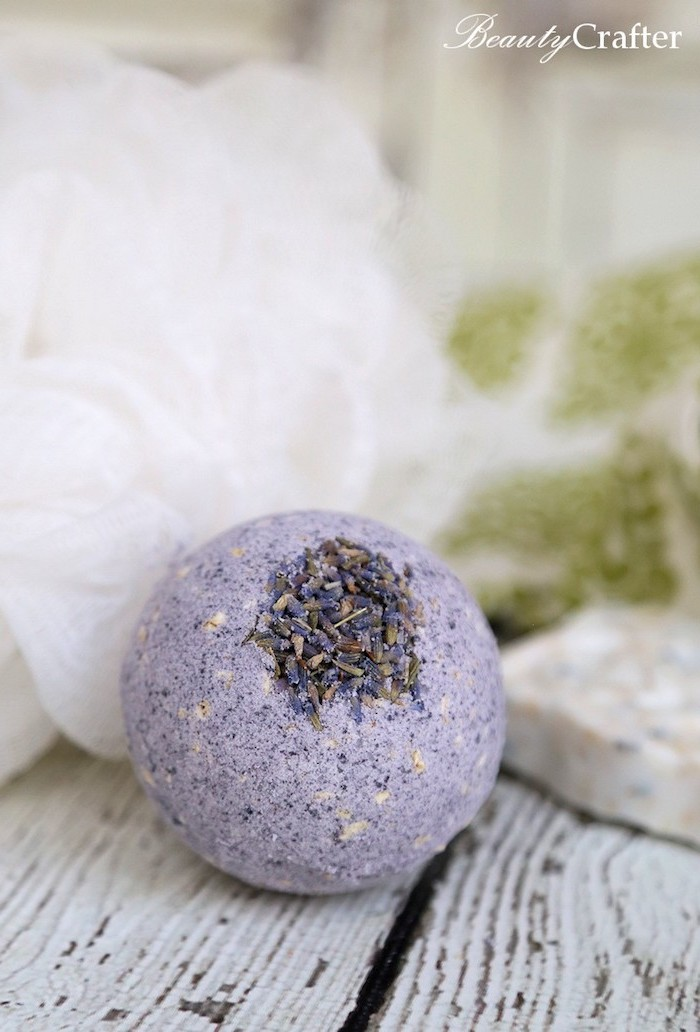 lavender bath bomb, pale violet in color, and spherical in shape, decorated with dried lavender petals, and placed on wooden surface