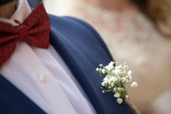 close up of a man's boutonniere, small bunch of baby's breath white flowers, mens summer wedding attire, dark blue suit jacket, worn with a white shirt and red bowtie
