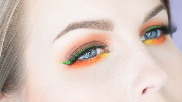 bright green yellow and orange eyeshadow, festival makeup, decorating the blue eyes of a pale woman, with ash blonde hair