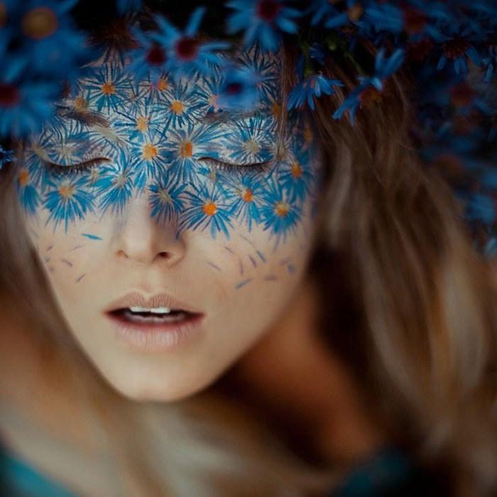 hand-painted blue and yellow flowers, covering the upper half of a girl's face, nude beige lipstick, makeup ideas, long brunette hair, with blue flower wreath