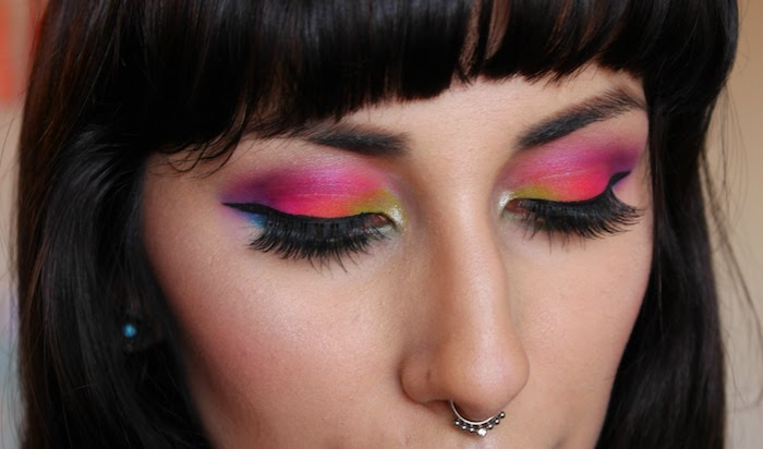 silver nose ring, worn by woman with dark hair and bangs, wearing fake lashes, makeup ideas, black eyeliner and eyeshadow, in yellow and orange, pink purple and blue