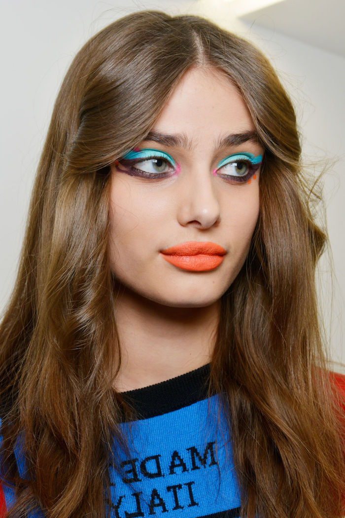 turquoise and black eyeliner, worn by famous model, with brunette hair, and bright orange lipstick, blue and black top, makeup ideas