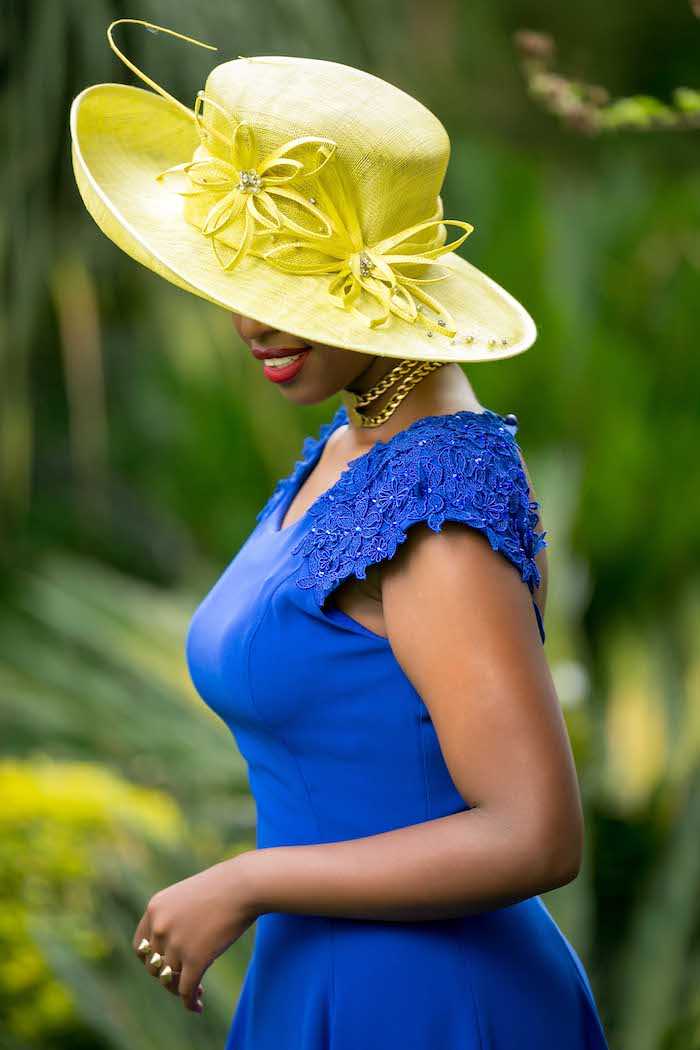 garden party attire, woman in vibrant blue dress, with embroidery and sequence detailing on the shoulder, wearing a fancy yellow hat