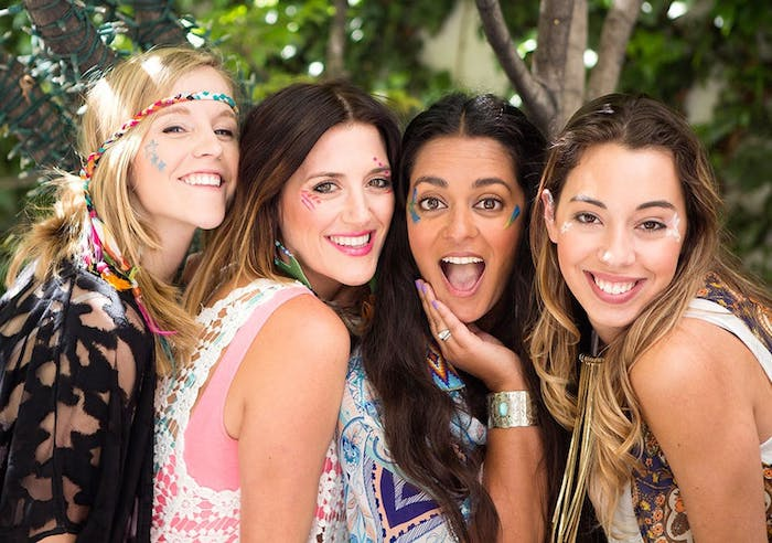 group of friends, made up of four women, smiling and posing for a photo, wearing boho style clothing, and face paint in different patterns and colors