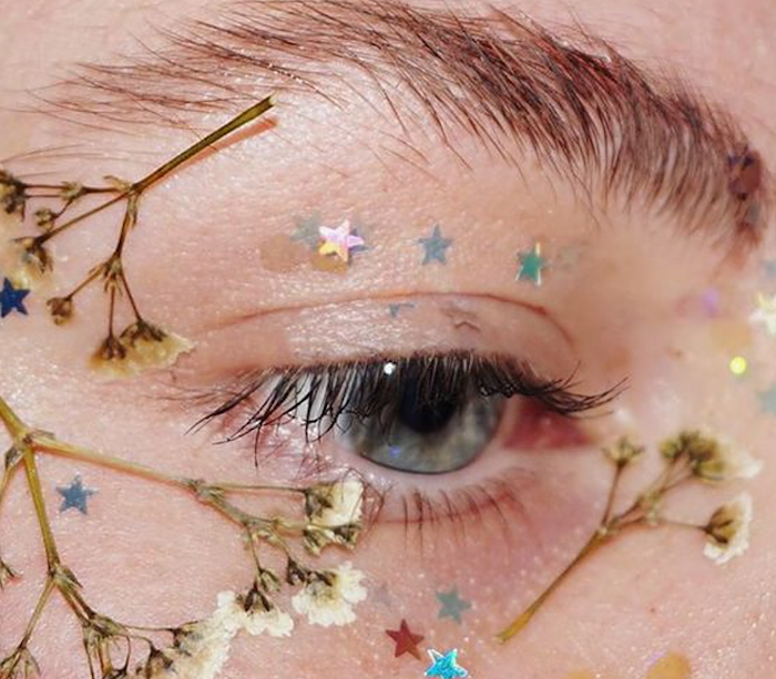 pressed tiny white dried flowers, stuck around a blue eye, seen in close up, with iridescent glitter stars, festival makeup, bushy brunette eyebrow