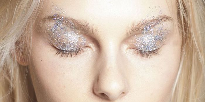 platinum blonde woman, with pale skin and closed eyes, wearing fine silver glitter, on her eyelids and eyebrows, make up ideas,
