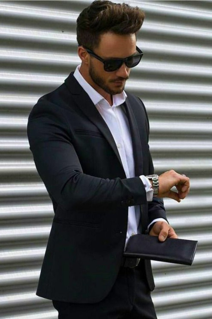 classical black suit, worn with a white shirt, by young man with sunglasses, black tie optional wedding, holding a black leather wallet, and looking at his watch