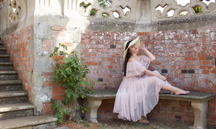 what is semi formal, barefoot young woman, with long dark brunette hair, wearing a floaty semi-sheer powder pink dress, with ruffles and a large straw hat, with a black ribbon