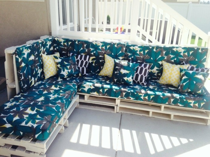 porch near a white staircase, with a big corner couch, made from pale wooden pallets, foam mattresses in blue, grey and white floral pattern