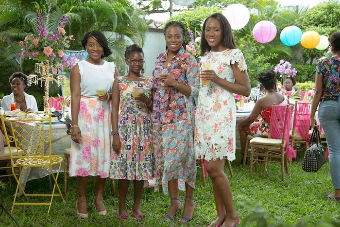 four young women, wearing multicolored floral print dresses, in different lengths and styles, dressy casual, garden party in the background