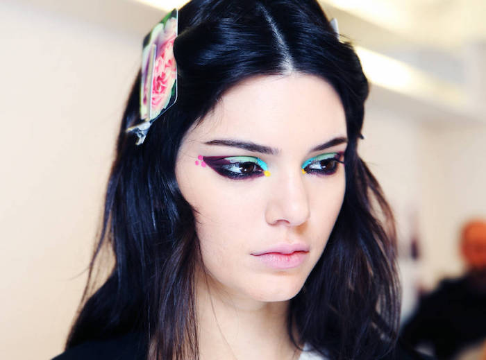 kylie jenner with black hair, floral hair ornament, pale pink matte lipstick, and multicolored eye makeup, featuring turquoise and green, pin and purple, black and yellow
