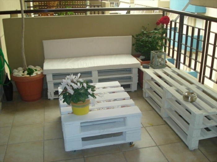 balcony covered with pale beige tiles, containing pallet outdoor furniture in white, sofa and a bench, coffee table with a flower pot