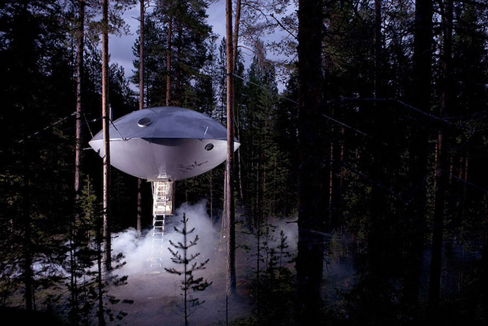 UFO shaped tree house, made from silver metal, suspended over the ground from several trees, and accessible through a ladder, cool tree houses, inside a dark forest