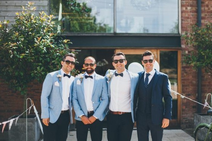 coordinated outfits on three men, pale blue blazers, white shirts and black bowties, mens wedding guest attire, standing next to the groom
