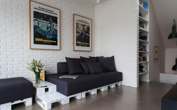 brick wall in white, inside a living room with a pallet sofa, made from white wooden pallets, covered in black sofa cushions