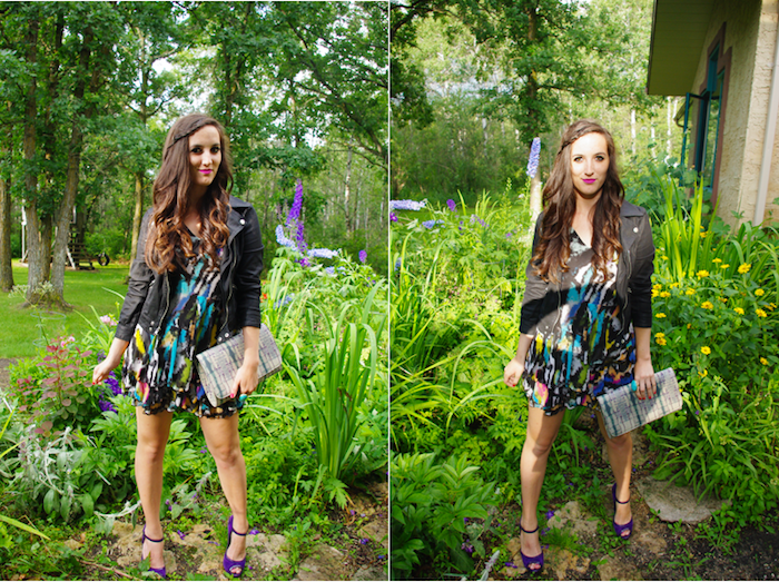 leather biker jacket in black, worn over multicolored mini dress, smiling brunette woman in dressy casual style, with purple high heel sandals, holding a large clutch bag