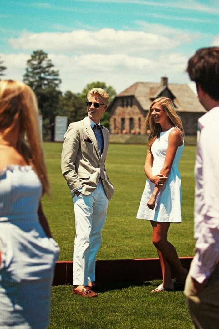 laughing couple standing on a green lawn, the man is dressed in white trousers and shirt, and beige blazer, what is cocktail attire for men, the woman sports a short white dress