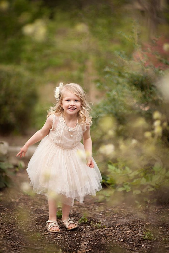 laughing little girl, with blonde curled hair, and smart pale pink tulle dress, wearing sandals and a flower ornament in her hair
