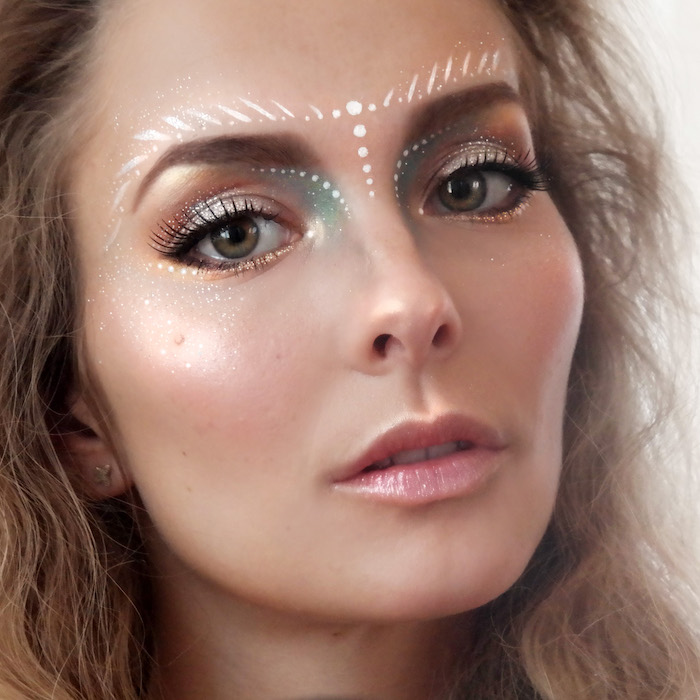 glossy pink highlighter, and shimmering pale pink lipstick, worn by slim woman, with silver and peach, pink and blue eyeshadow, make up ideas, white face paint