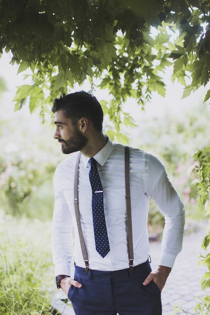 bearded brunette man, wearing a white shirt, with brown suspenders, dark patterned tie, and dark blue trousers, mens wedding guest attire, trees and grass nearby